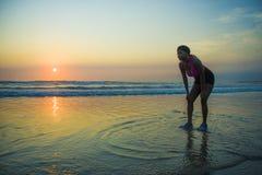 冷却呼吸的年轻运动和疲乏的非裔美国人的赛跑者妇女被用尽在连续锻炼以后在美丽的海滩太阳 库存照片