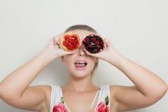 冷却拿着甜点心用莓果的白肤金发的女孩并且报道h 库存图片