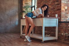 冷却穿着白色上面和牛仔布短裤的现代深色的女孩站立倾斜在桌,当使用智能手机时 免版税库存照片