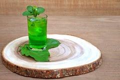 冷和刷新的石灰和薄荷的绿色水在一块玻璃在木头 免版税库存照片