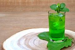 冷和刷新的石灰和薄荷的绿色水在一块玻璃在木头 库存图片