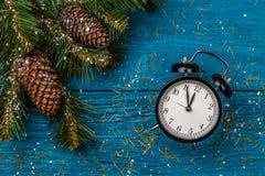 冷杉、锥体和时钟,雪圣诞节分支照片  库存图片