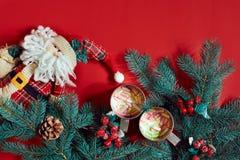 冷杉分支、玩具圣诞老人和两个杯子可可粉用在红色背景的蛋白软糖 库存照片