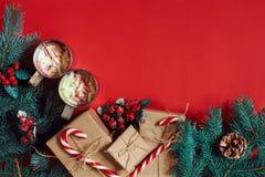 冷杉分支、礼物盒和两个杯子可可粉用在红色背景的蛋白软糖 免版税库存照片