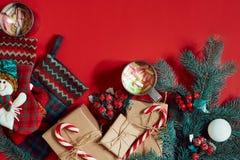 冷杉分支、礼物盒和两个杯子可可粉用在红色背景的蛋白软糖 库存图片