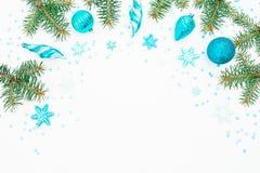 冷杉分支、蓝色装饰和雪花圣诞节框架在白色背景 平的位置,顶视图 免版税库存图片