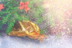 冷杉分支与锥体,并且红色鞠躬在灰色具体背景顶部 新年圣诞节 与礼品的金袋子 免版税库存照片