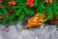 冷杉分支与锥体,并且红色鞠躬在灰色具体背景顶部 新年圣诞节 与礼品的金袋子 免版税库存图片