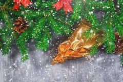 冷杉分支与锥体,并且红色鞠躬在灰色具体背景顶部 新年圣诞节 与礼品的金袋子 免版税图库摄影