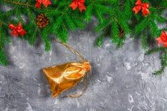 冷杉分支与锥体,并且红色鞠躬在灰色具体背景顶部 新年圣诞节 与礼品的金袋子 库存图片