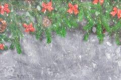 冷杉分支与锥体,并且红色鞠躬在灰色具体背景顶部 新年圣诞节 文本的空位 图库摄影