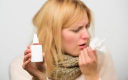 冷流感解决 流鼻水和寒冷的其他症状 鼻下落瓶 鼻孔喷射鼻涕补救 妇女 免版税库存照片