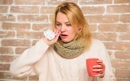 冷流感解决 补救应该帮助打冷的快速的妇女感觉非常不适打喷嚏 围巾举行茶杯子的女孩 库存图片