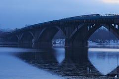 冷淡的清早 在水反映的地铁桥梁 第一列地铁火车在桥梁移动 Kyiv 乌克兰 库存照片