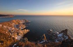 冷的冬天早晨的岩石海岸 免版税库存图片