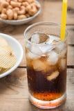 冷的可乐冰了在一块玻璃的饮料在木背景 库存照片