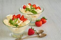 冷的夏天点心用切的草莓,在玻璃碗的乳酪奶油在灰色厨房用桌上 冷甜点用薄菏 库存照片