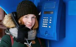冷的季节成套装备的美丽的年轻红头发人女孩使用街道蓝色投币式公用电话 图库摄影