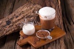 冷的巧克力牛奶饮料和巧克力块在木背景 免版税图库摄影