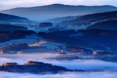 冷的早晨在Sumava国家公园、小山和村庄雾的和霜,有薄雾的看法在捷克风景,蓝色冬天场面, Tr 免版税库存照片