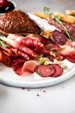 冷的熏制的肉板材 传统意大利开胃小菜,切板用蒜味咸腊肠,熏火腿,火腿,猪排,橄榄 库存图片