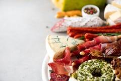 冷的熏制的肉板材 传统意大利开胃小菜,切板用蒜味咸腊肠,熏火腿,火腿,猪排,橄榄 库存照片