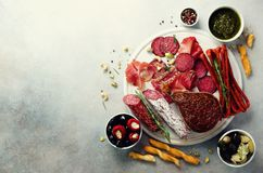 冷的熏制的肉板材 传统意大利开胃小菜,切板用蒜味咸腊肠,熏火腿,火腿,猪排,橄榄 免版税库存照片