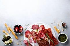 冷的熏制的肉板材 传统意大利开胃小菜,切板用蒜味咸腊肠,熏火腿,火腿,猪排,橄榄 免版税库存图片