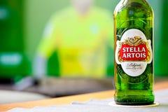 冷的瓶在电视背景,与啤酒概念,突出的品牌的socer时间的史特拉Artois啤酒 免版税库存图片