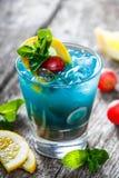 冷的蓝色酒精鸡尾酒用柠檬、葡萄和薄菏在玻璃在木背景 夏天饮料 免版税库存图片