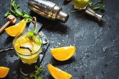冷的酒精夏天柑橘鸡尾酒用桔子和薄菏在玻璃和在黑暗的石背景 做酒吧工具, sha的鸡尾酒 免版税库存照片
