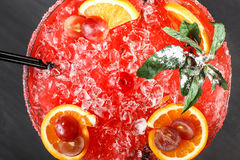冷的酒精西瓜鸡尾酒用桔子、薄菏、冰和葡萄在大葡萄酒杯在黑木背景 免版税库存照片