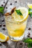 冷的酒精鸡尾酒用柠檬、石灰和薄菏在玻璃在木背景 夏天饮料 免版税库存照片