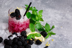 冷的饮料用薄菏和黑莓在一块巨大的玻璃在灰色背景,切片柠檬用莓果和薄菏在a 免版税图库摄影