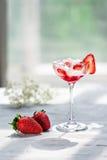 冷的鸡尾酒用伏特加酒、草莓糖浆、新鲜的草莓和被击碎的冰在玻璃在轻的背景 库存照片