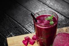 冷,自然和有机红色甜菜汁 一杯甜菜根在木背景喝 在书桌上的立方体切的甜菜 库存照片