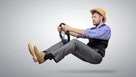 冷却一个帽子的有胡子的人有方向盘的, 免版税库存照片