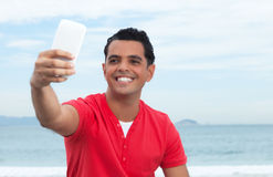 冷却做与电话的红色衬衣的拉丁人selfie 库存照片