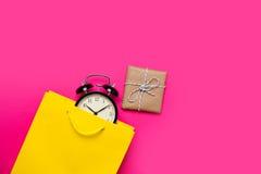 冷却在美丽的黄色购物袋的黑闹钟和逗人喜爱 免版税库存图片