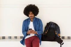冷却坐与手机和袋子的旅行人 免版税图库摄影