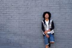 冷却有非洲倾斜的年轻人对墙壁 免版税库存照片