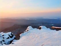 冷冻用新鲜的粉末雪盖的下落的树干,从有雾的谷增加的石岩石峰顶。在岩石的冬天有薄雾的日出。 免版税库存图片