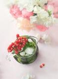 冷却的薄荷的戒毒所浇灌与荚莲属的植物分支和桃红色和白色牡丹花束在粉红彩笔背景的 免版税库存图片