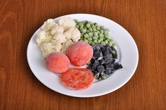 冷冻蕃茄、芦笋、豌豆和花椰菜在板材 免版税库存照片