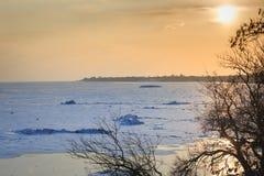 冻海在冬天,冰小丘,反射的海岸在太阳中水发出光线在日落 免版税库存照片