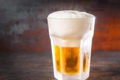 冻玻璃用低度黄啤酒和泡沫一个大头在老d的 库存图片