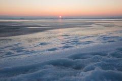 冻结的海运日落 在冬时的美好的自然海景 对天际的不尽的冰 产品安置的冰表面 免版税库存图片