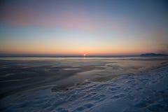 冻结的海运日落 在冬时的美好的自然海景 对天际的不尽的冰 产品安置的冰表面 库存照片