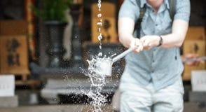 水净化的游人在日本寺庙入口  免版税库存图片