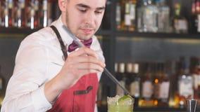 准备一个刷新的鸡尾酒的专业侍酒者装饰它与切片石灰 影视素材